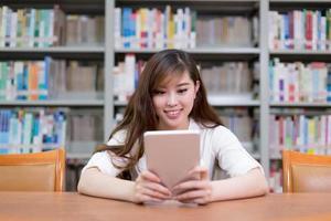 Hermosa estudiante asiática con tableta digital en la biblioteca foto