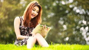 Asian woman using digital tablet in park photo
