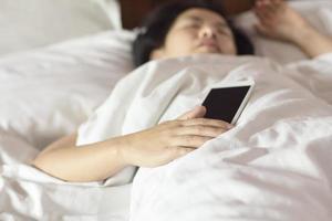 Mujer durmiendo en la cama y sosteniendo un teléfono móvil.