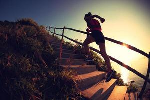fitness woman runner trail running on seaside mountain stairs, photo