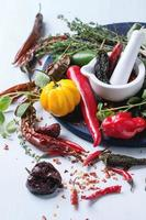 Assortment of chili peppers and herbs photo