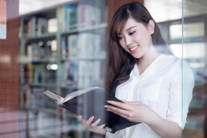 asian beautiful female student holding book in library portrait