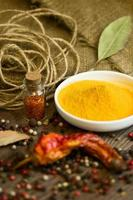 Turmeric in saucer with spices photo