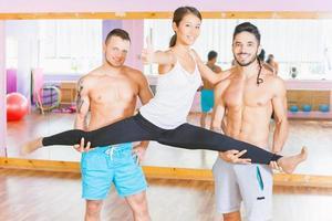 Young beautiful asian woman doing split between two guys