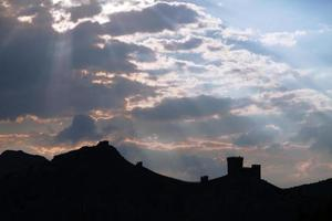 Genoese fortress silhouette with blue sky and clouds
