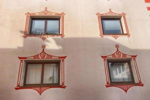 squared glass windows with brown frame and artistic border