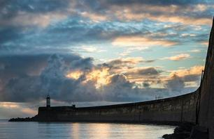 Beautiful vibrant sunrise sky over calm water ocean with lighthouse photo