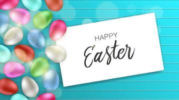 huevos coloridos con tarjeta de pascua feliz en madera