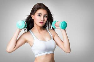 Healthy hispanic young asian woman with dumbbells working out photo