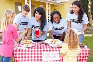 mujeres y niños que ejecutan venta de pasteles de caridad foto