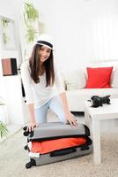 cheerful young beautiful ethnic brunette closing her suitcase preparing trip