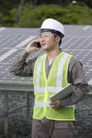Asian engineer checking solar panel setup.