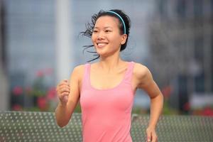 mujer asiática sana corriendo en la ciudad moderna foto