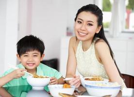 chino madre e hijo sentados en casa comiendo una comida foto