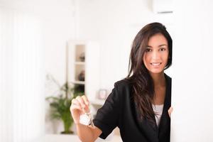 vrolijke jonge zakenvrouw makelaar geeft sleutels nieuw huis