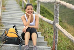 young asian woman hiker sit mountain stairs photo