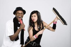 Young man & woman using household items as fake instruments photo