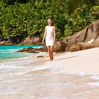 mujer con vestido en la playa en seychelles