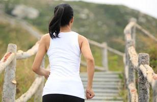 mujer corredor corriendo en las escaleras de montaña