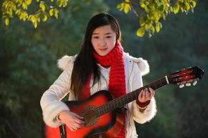 Asian girl playing the guitar