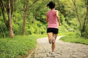 Runner athlete running on forest trail. photo