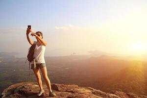 hiking woman taking photo with smart phone on mountain peak