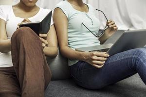 dos estudiantes universitarios sentados en el suelo y trabajando foto