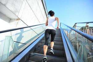 Atleta corredor corriendo en las escaleras de la escalera mecánica. foto