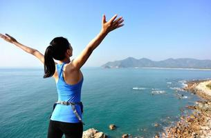 cheering woman hiker raised arms to blue sea