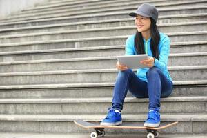 joven skater usar su tableta digital sentarse en las escaleras foto