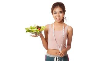 Asian slim girl with measuring tape and salad