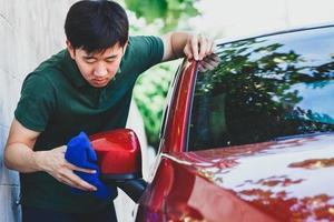 jonge Aziatische man in uniform schoonmaken en wassen van een auto