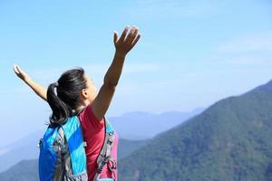 feliz senderismo mujer brazos abiertos en el pico de la montaña foto