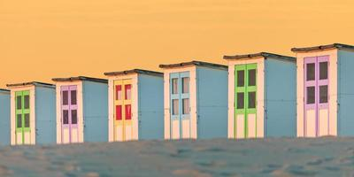 Row of old wooden beach cabins during sunset