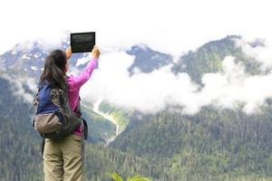woman hiker taking photo with digital tablet