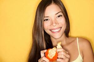 mujer sonriente pelando naranja sobre un fondo amarillo