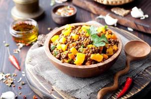Lentil with carrot and pumpkin ragout in a wooden bowl.