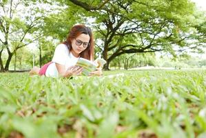 Young Woman Lying Down and Reading Book in the Park