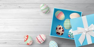 Blue gift box with Easter eggs on wood texture vector