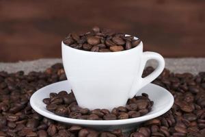 composición de la taza blanca con primer plano de granos de café
