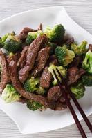 carne asiática com brócolis e pauzinhos. vista superior vertical