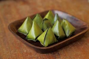 Thai dessert wrapped in banana leaves on wooden dish.
