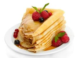 Delicious pancakes with berries and honey isolated on white photo