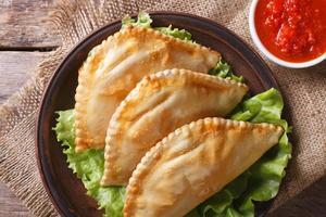 empanadas en sausclose-up. horizontaal bovenaanzicht, rustiek