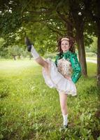 giovane bella ragazza in abito da ballo irlandese ballare all'aperto