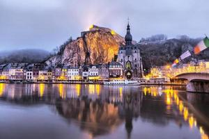 Church and cliff reflecting in river Meuse, Dinant