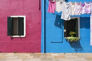 Two colorful houses of Burano Island with laundry, Venice, Italy