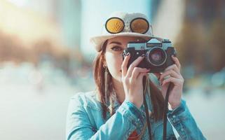 Chica hipster haciendo foto con cámaras retro, se centran en la cámara