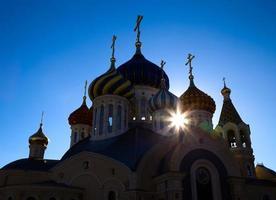 igreja ortodoxa contra o céu azul com erupção solar