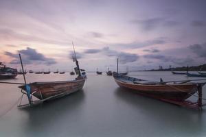 violette hemel met houten boten op de zee